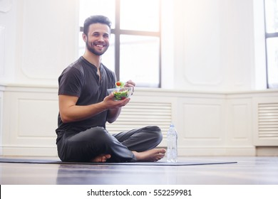 Yoga men with a bowl of vegetable salad, a bottle of water wearing a sportive outfit. Healthy lifestyle concept