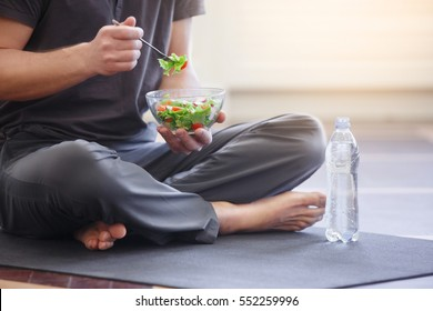 Yoga men with a bowl of vegetable salad, a bottle of water wearing a sportive outfit. Healthy lifestyle concept, close up