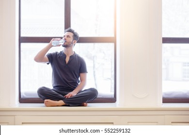 Yoga men drinking water while holding yoga mat in fitness class. Healthy lifestyle concept