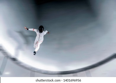 Yoga men run in free fall. Wind tunnel skydiving.  White and orange suit.  Indoor skydiving sport