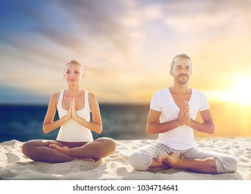 yoga , mindfulness, harmony and people concept - happy couple meditating on beach