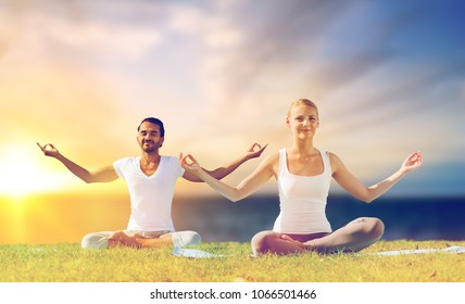 yoga , mindfulness, harmony and people concept - happy couple meditating in lotus pose outdoors over sea background