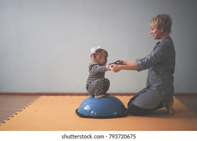 yoga mom and Toddler with Down syndrome on Balancing Ball Yoga, development of children, happy childhood