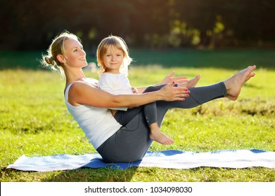 Yoga  mother practicing sitting boat yoga pose with her little daughter in the park