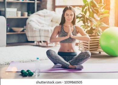 Yoga is my lifestyle! Sportive thoughtful pensive beautiful charming woman with close eyes wearing sporty pants and top is practicing yoga at home sitting on purple mat, wellbeing concept