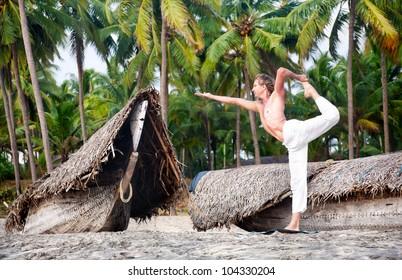 Yoga natarajasana dancer pose by fit man in white trousers on the beach near the fishermen boats in Varkala, Kerala, India