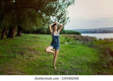 Yoga in nature. Balances on the legs, development of the vestibular apparatus, Vrikshasana. The girl on the river bank in the park is meditating to the music with headphones.
