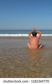 yoga nude man on water sand ocean sea summer alone in beach concept of freedom nudism