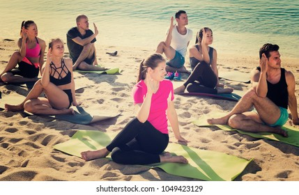 Yoga on beach, group of people practicing healthy lifestyle