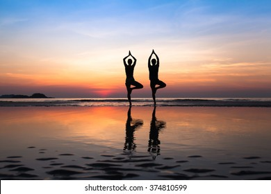 yoga on the beach, group of people practicing healthy lifestyle