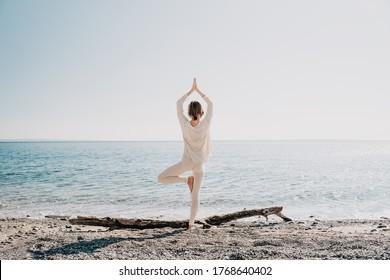Yoga en la playa. Mujer practicando yoga en la costa del océano. Hermosa chica relajándose junto al mar. Foto tranquila, serena, minimalista con espacio para copiar. Estilo de vida activo saludable, vitalidad, zen.