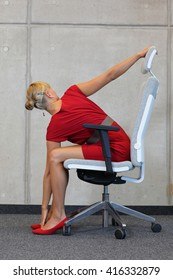 yoga on chair in office - business woman exercising, back view