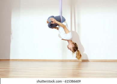Yoga on the horn. A woman is practicing yoga on a hose, aerial yoga