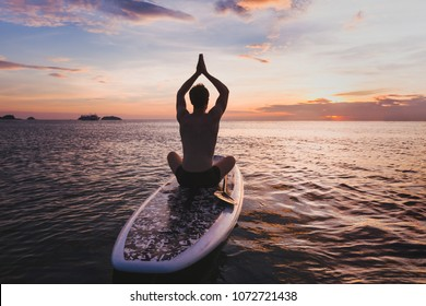 yoga on SUP, silhouette of man sitting in lotus position on stand up paddle board