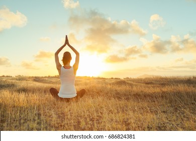 Yoga outdoor. Happy woman doing yoga exercises. Yoga meditation in nature. Concept of healthy lifestyle and relaxation. Woman practicing yoga on the grass