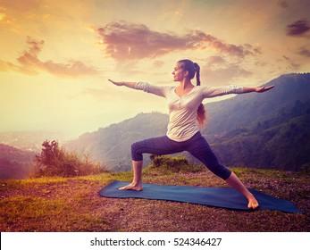 Yoga outdoors - sporty fit woman doing Ashtanga Vinyasa Yoga asana Virabhadrasana 2 Warrior pose posture in mountains. Vintage retro effect filtered hipster style image.