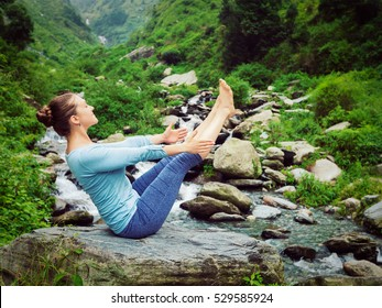 Yoga outdoors - sporty fit woman doing Ashtanga Vinyasa Yoga asana Navasana boat pose in Himalayas at tropical waterfall. Himachal Pradesh, India. Vintage retro effect filtered hipster style image.
