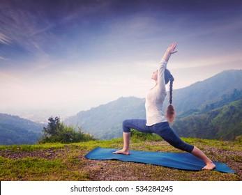 Yoga outdoors - sporty fit woman doing Ashtanga Vinyasa Yoga asana Virabhadrasana 1 Warrior pose posture in HImalayas mountains on sunset. Vintage retro effect filtered hipster style image.