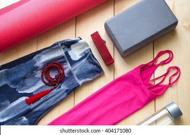 Yoga outfit on wooden background, top view