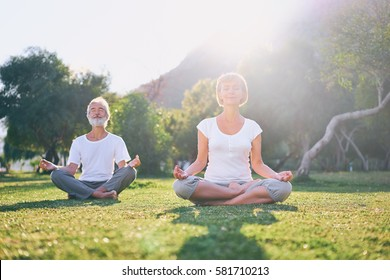 Yoga at park. Middle aged family couple  sitting in lotus pose on green grass. Concept of calm and meditation.