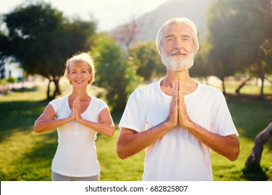 Yoga at park. Senior family couple  outdoors. Concept of calm and meditation.