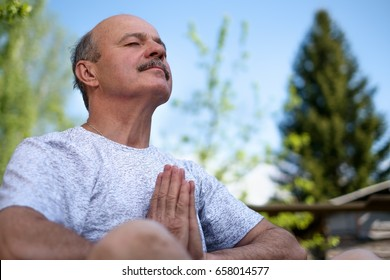 Yoga at park. Senior man with mustache with namaste sitting.Concept of calm and meditation.