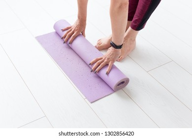 Yoga, peopel concept - Close up of woman rolling her mat after a yoga class