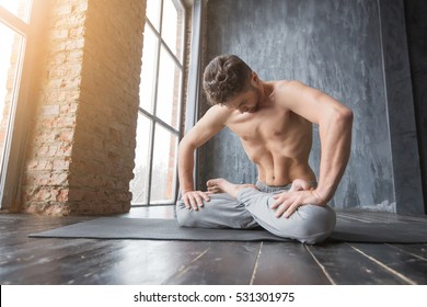 Yoga. Portrait of yogi men doing yoga exercise on black mat, he breath and performing Upward abdominal lock and show rectus abdominis, Uddiyana Bandha. Young men workout in urban studio.
