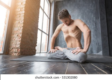 Yoga. Portrait of yogi men doing yoga exercise on black mat, he breath and performing Upward abdominal lock, Uddiyana Bandha. Young men workout in urban studio.