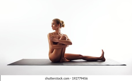 Yoga pose demonstrated by beautiful woman. Nude woman sitting on exercise mat performing yoga over white background.