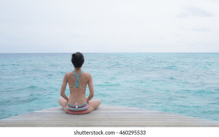 Yoga pose in front of clear blue ocean