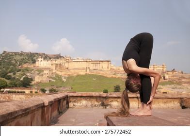 Yoga pose Standing forward fold or Uttanasana  at Amber fort, Jaipur, India