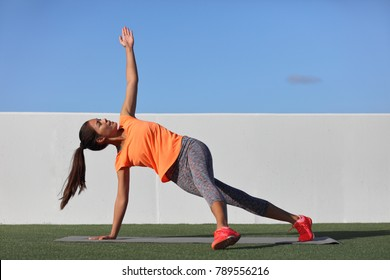 Yoga pose variation fitness girl doing the fallen triangle assited with leg. Asian woman doing side plank with lateral leg raise. Planking exercise for body core, bodyweight workout at home gym.