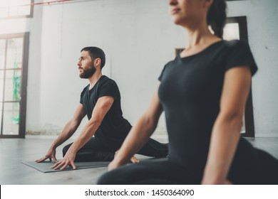 Yoga Practice Exercise Class Concept. Two beautiful people doing exercises.Young woman and man practicing yoga indoors