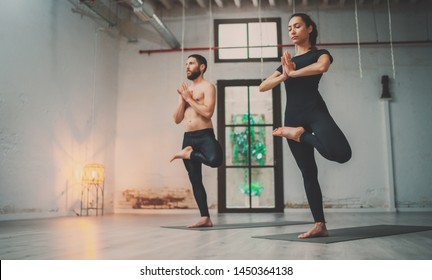 Yoga Practice Exercise Class Concept. Young woman and man practicing yoga indoors. Two sporty people doing exercises