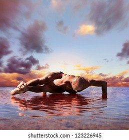 Yoga practice. Man doing  eight arcs yoga pose into the water at sunset time