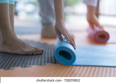 Yoga practitioner folding yoga mat after class at studio. Workout lifestyle for meditation, body balance vs body strength. Yoga mat is equipment support practitioner during workout. Healthcare concept