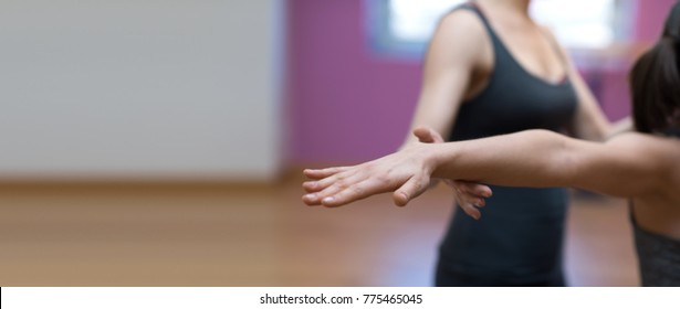 Yoga professional instructor helping a woman to stretch her arms and balance