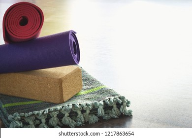 Yoga props selection in balance. Folded cotton mat, cork block and colorful rolled mats on studio wooden floor