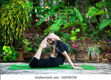 Yoga Raja Kapotasana backward bending pose by woman in black cloth in the garden with palms, banana trees and plants in the pots