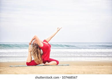 Yoga raja kapotasana dove pose by young woman with long hair in red cloth on the beach at ocean background