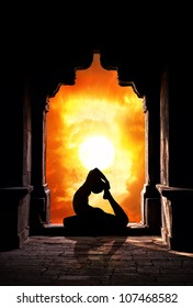 Yoga raja kapotasana pigeon pose by man silhouette in old temple at dramatic sunset sky background. Free space for text
