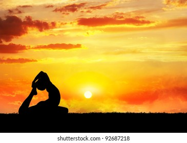 Yoga raja kapotasana pigeon pose by man silhouette at sunset sky background. Free space for text and can be used as template for web-site