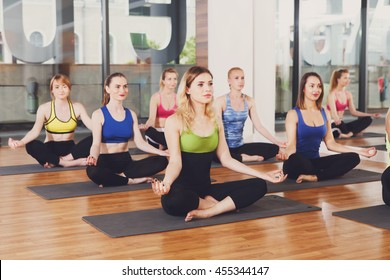 Yoga relaxation. Group of young women in sport class making exercises. Girls do meditation pose for relax after training. Healthy lifestyle in fitness club
