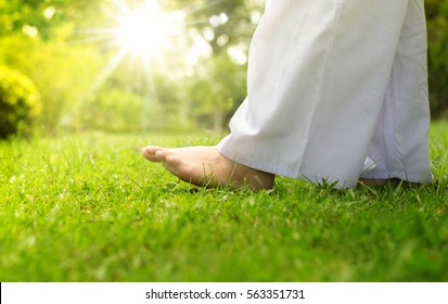 Yoga relaxation. Woman buddhist walking on green grass for meditation over sunlight