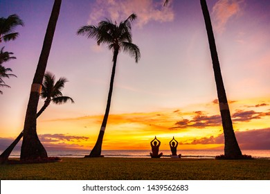 Yoga retreat on tropical summer holiday meditation people couple meditating in lotus pose with praying hands in sunset glow silhouettes on beach.