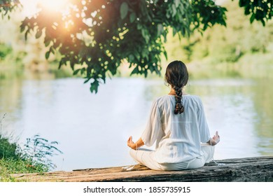 Yoga Retreat. Peaceful young woman sitting in lotus position and meditating by the lake