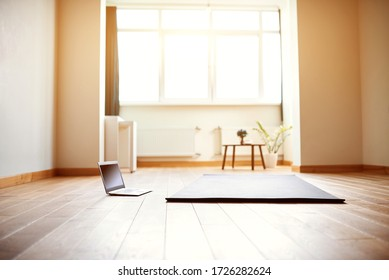 yoga room with big light window in modern flat. Yoga mat and computer on the floor, no people.