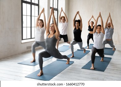 Yoga session led by caucasian woman coach, millennial athletic multiracial group of people practising posture with female instructor, doing Warrior one Virabhadrasana I asana, workout full length view