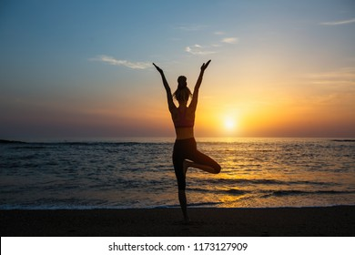 Yoga silhouette meditation fitness woman on the ocean during amazing sunset.